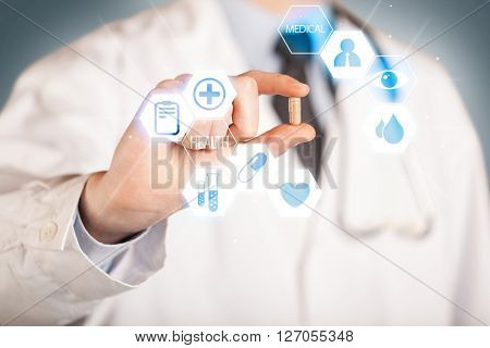 A pill is being held in the hand of a doctor dressed in white, illustrated with blue signs