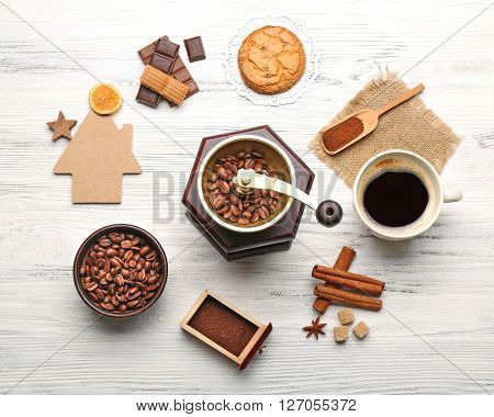 Coffee mill, spices and chocolate on wooden table, top view