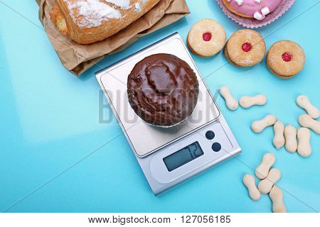 Chocolate cupcake and digital kitchen scales on blue background