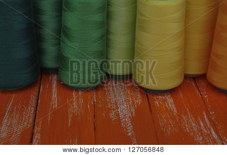 Colored threads in coils on an orange background old wooden table