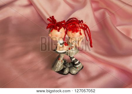 souvenir statuette of a boy and a girl on a pink silk