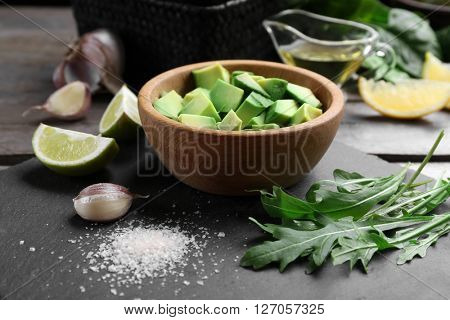 Diced avocado in wooden bowl with lime, garlic and arugula on slate plate