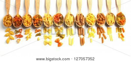 Different types of dry pasta in wooden spoons on white background
