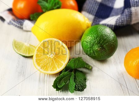 Set of different citrus fruit on light wooden table