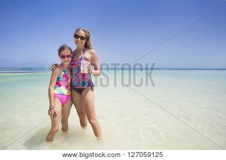 Beautiful Woman and her cute daughter enjoying a fun day while on a tropical beach vacation. Woman is drinking a pina colada drink.