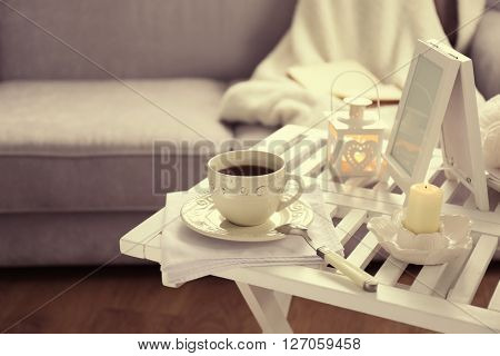 Cup of tea on coffee table in the room, close up