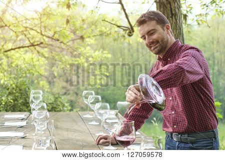 Man pour red wine smiling in beautiful cottage