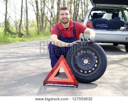 Confidence mechanic outdoor repairing a vehicle breakdown