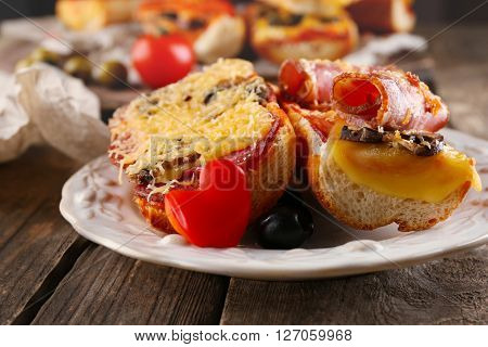 Hot pizza baguettes with bacon, salami and mushrooms on wooden table