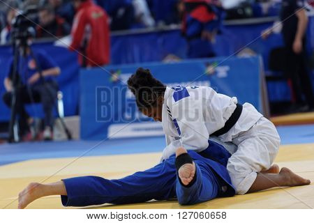 ST. PETERSBURG, RUSSIA - APRIL 16, 2016: Match Ulyana Minenkova of Belarus (blue) vs Sarah Leonie Cysique of France during the Junior European Judo Cup. 346 athletes participated in the competition