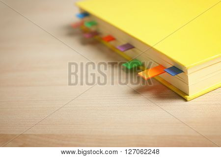 Yellow notebook with bookmarks on wooden table