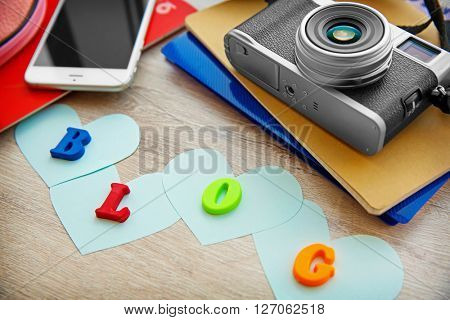The word BLOG from colorful letters, mobile phone and retro camera on wooden background