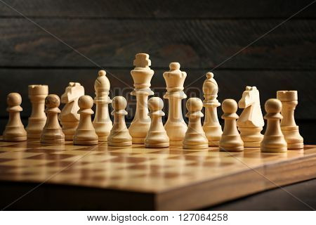 Chess pieces and game board on wooden background