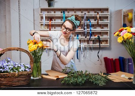 Smiling charming young woman florist taking care of yellow roses in flower shop