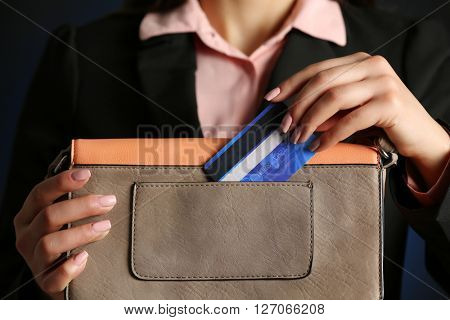 Businesswoman putting her card in a purse