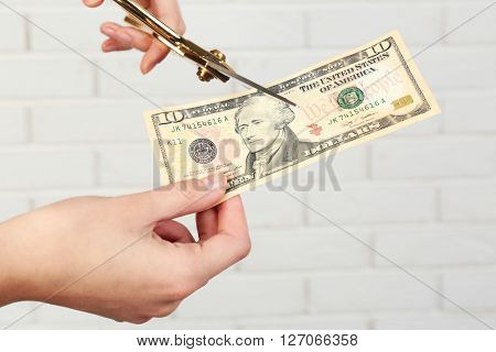 Hands with scissors cutting money on white brick wall background