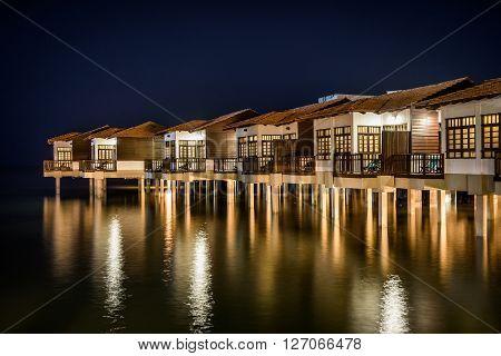 A shot of ocean view villas built on stilts.