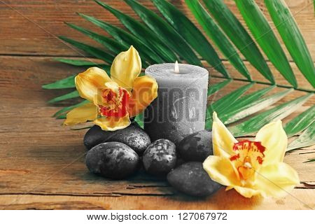 Spa stones with beautiful flowers and candles on wooden background