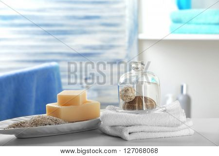 Soap with salt, towels and shells on bathroom table