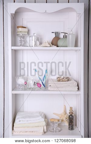 Bathroom set with towels, starfish and toothbrushes on a light shelf