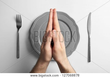 Male holding hands together over grey plate, isolated on white