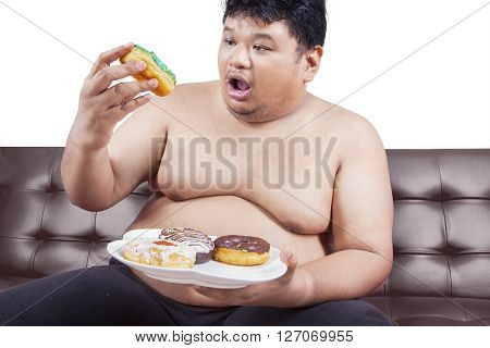 Picture of a young obese man sitting on brown sofa and enjoy donuts isolated on white background