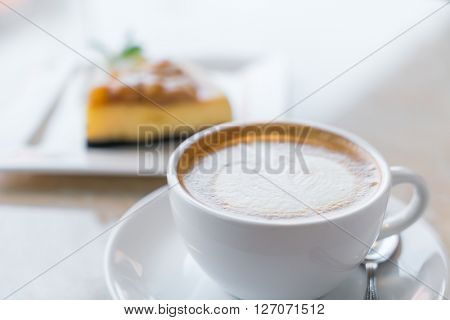 Cup of coffee and cheesecake piece