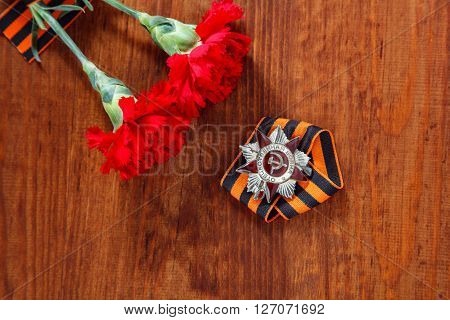 Order Of The Patriotic War In St. And Two Red Flower And George Ribbon On Wooden