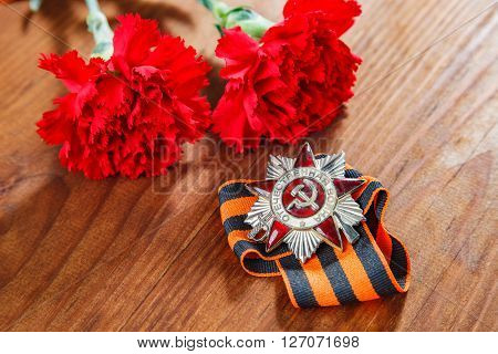Symbols Of Victory In Great Patriotic War Two Red Flower And George Ribbon On Table