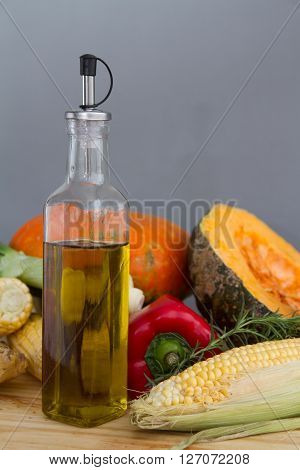 Olive Oil Bottle With Organic Pumpkin Squash With Fresh Vegetables: Corn, Red Peppers, Scallion, Ros
