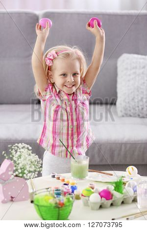 Happy little girl painting Easter eggs, indoors