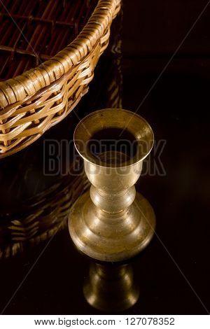 Old brass candlestick on black mirror background