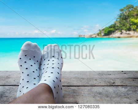 feet on wooden floor over beach background Relaxtion on vacation concept