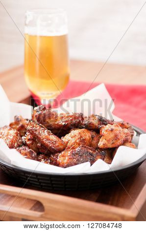 tasy hot spicy chicken wings with a cold beer