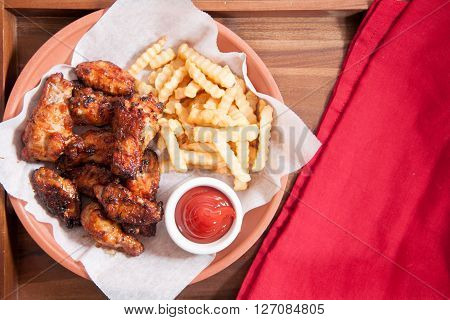hot and spicy buffalo style chicken wings and fries in a basket