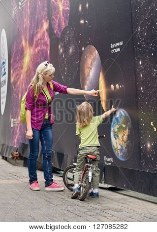 Family studies banner solar system about planetarium. MOSCOW, RUSSIA