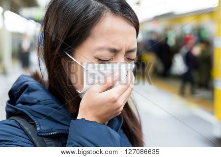 Asian woman wearing face mask at train station