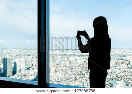 Silhouette of woman shooting photo on Tokyo city
