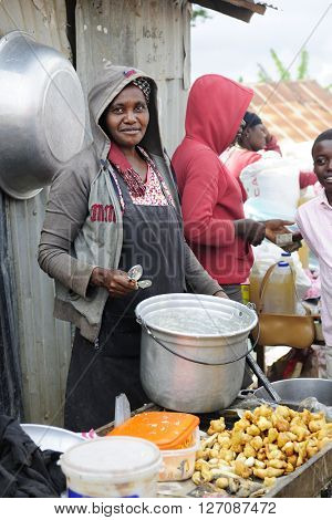 FOND BAPTISTE, HAITI - FEBRUARY 29, 2016:   An unidentified woman selling fried chicken at a weekly market in Fond Baptiste..
