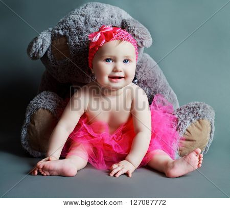 adorable six months old baby with a toy against grey studio background