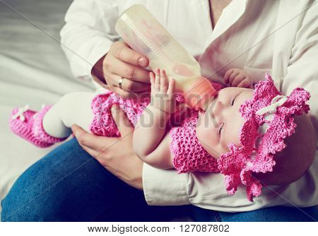 father feeding his four months old baby with milk from the bottle.