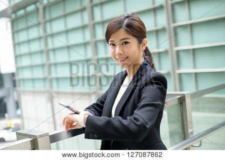 Businesswoman use of cellphone to connect with smart watch