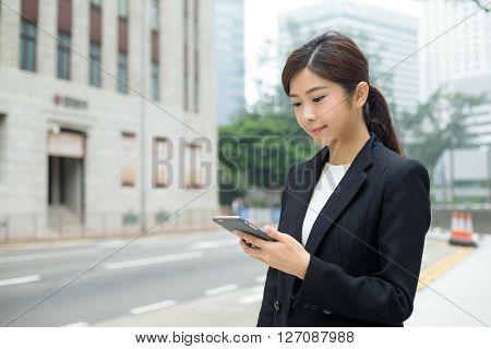 Businesswoman sending sms on mobile phone