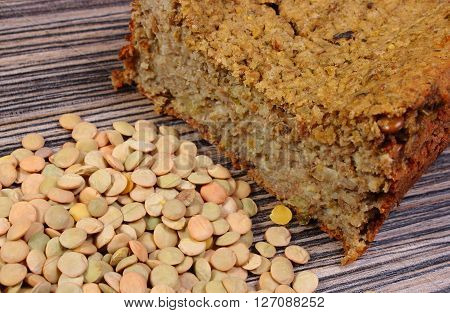 Raw green lentil and fresh homemade baked pie of lentil on wooden background healthy food and nutrition