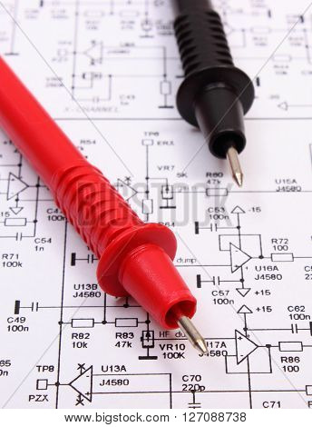 Cable of multimeter on diagram of electronics printed circuit board drawing and tools for engineer jobs