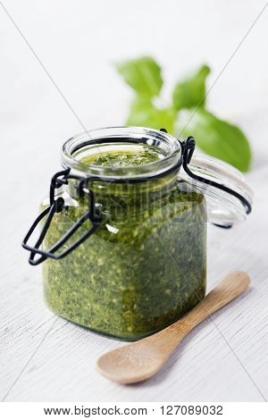 Homemade traditional basil pesto on a rustic wooden table