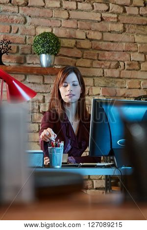 Young businesswoman sitting at desk, working.