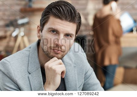 Portrait of thoughtful handsome businessman sitting with hand on chin.