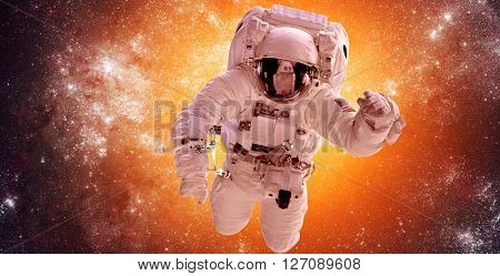 Astronaut in outer space against the backdrop of the stars nebula background. Elements of this image furnished by NASA.