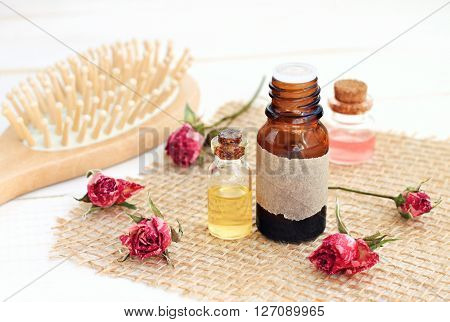 Rose essential oil, rose water, hair brush. Aromatic herbal essences hair care.